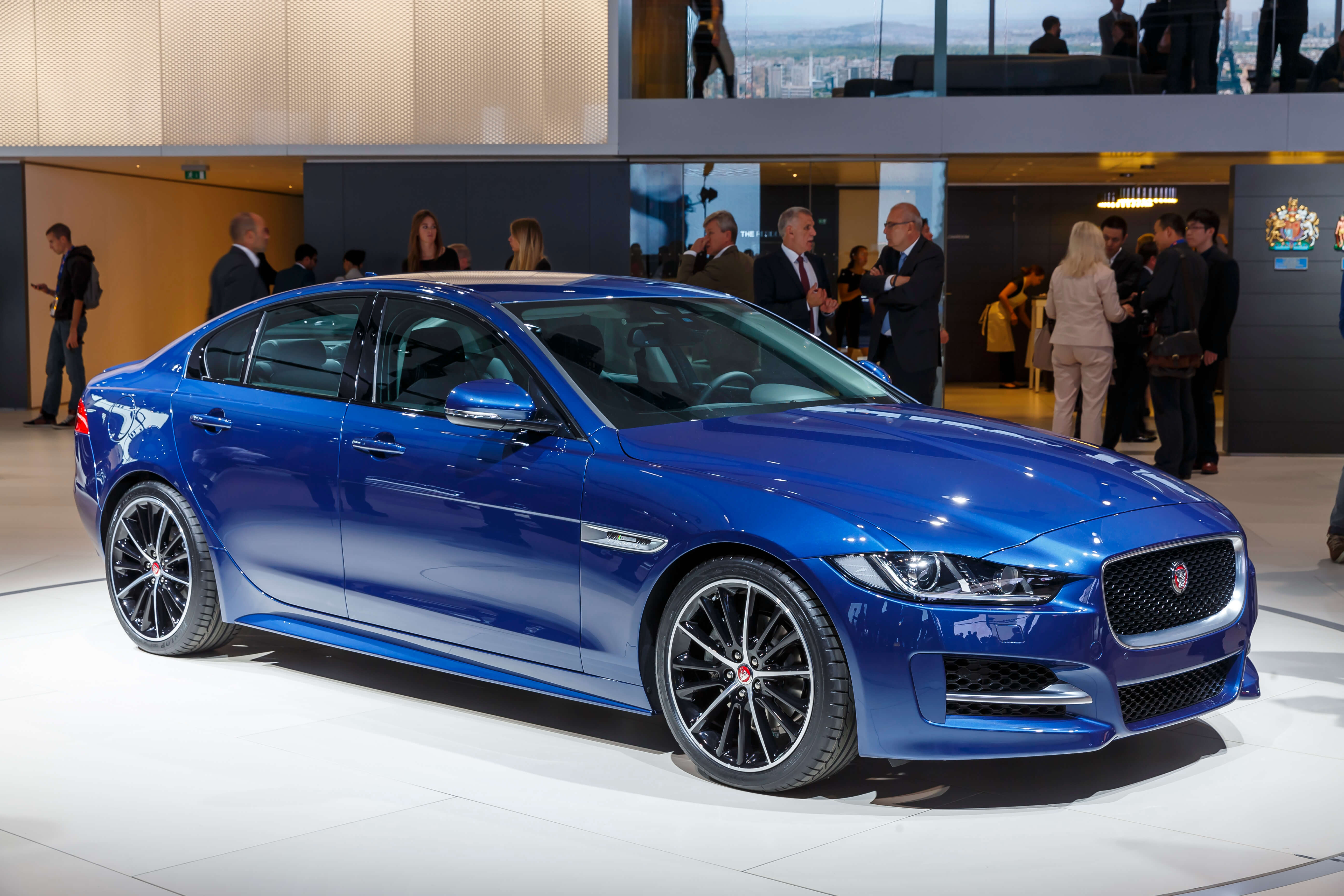 Blue automobile in a leasing vs buying a car showroom and people around the car.