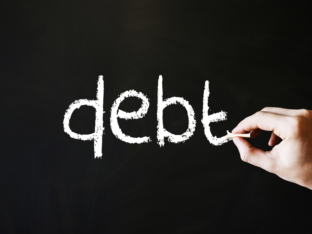 Hand Writing Debt on a blackboard