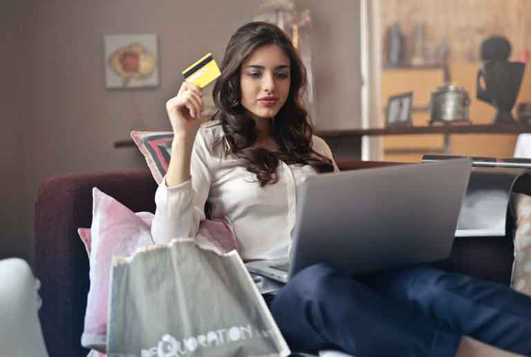 woman checking on her laptop while holding a yellow bank card